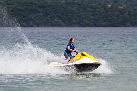 throttle: Guanacaste, Costa Rica- July 25: young woman riding a wave runner in Nacascolo Beach. July 25 2017, Guanacaste, Costa Rica.