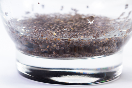 close up of a glass with water and chia seeds with a gummy texture