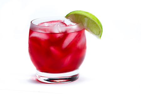 close up of a red cocktail served on the rocks garnished with a lime isolated on a white background