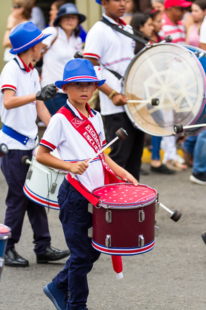 typical: School children marching in the town square playing percussion instruments for the independence day parade.