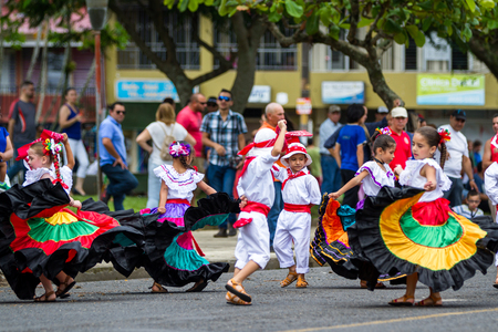 Young children celebrating independence day in Costa Rica with traditional clothing and dancing.