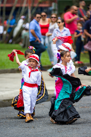 Young children celebrating independence day in Costa Rica with traditional clothing and dancing. Редакционное