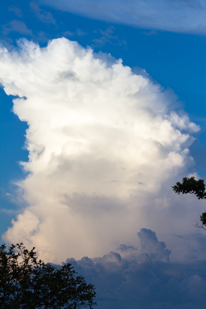 towering cloud reaching up towards the sky as the sun brightens it before it sets