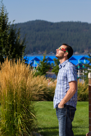 Coeur d Alene, Idaho - August 21 : young man watching the eclipse with protective eye glasses. August 21 2017, Coeur d Alene Idaho.