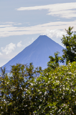 clear afternoon view of the Arenal volcano from across the lake