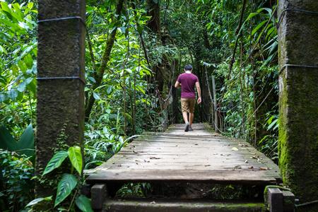 hombre caminando sobre un puente colgante en el Parque Nacional Tenorio, con una exuberante vegetación verde alrededor