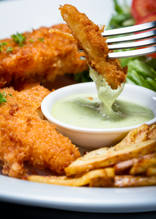 tenders: close up of a plate of fish and chips served with a side salad and a dipping sauce