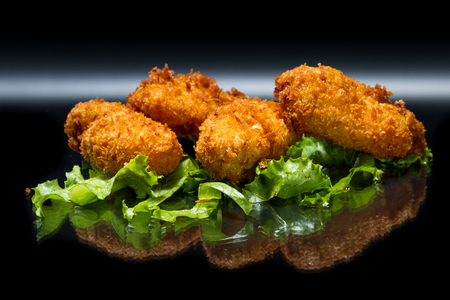 crispy fired croquettes stuffed with potato and salmon served on a bed of lettuce