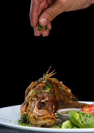whole fish deep fried and served with a side salad being garnished with parsley