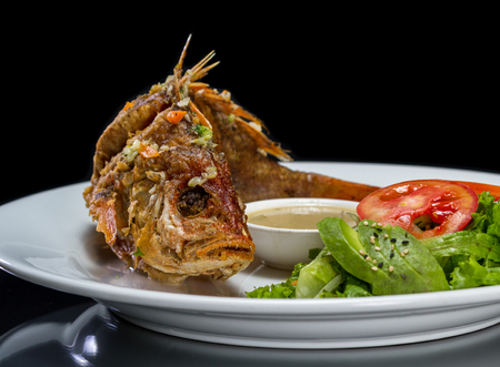 whole fish deep fried and served with a side salad Stock Photo