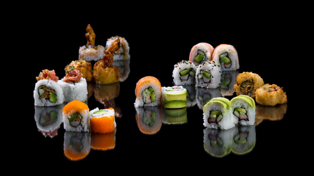 variety of colorful sushi rolls placed on a black reflective background