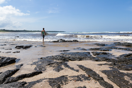 Langosta Beach, Costa Rica - October 12: Surfer walking into the ocean ready to catch some waves. October 12 2017, Langosta Beach Costa Rica.