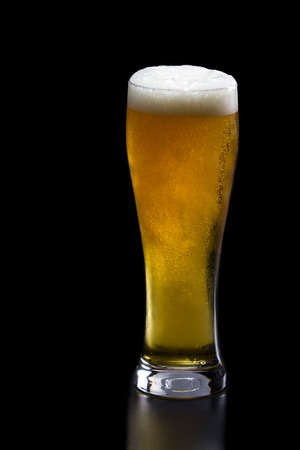 refreshing golden beer served on a tall glass over a black background