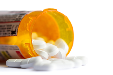 close up of a group of white tablets with an out of focus prescription bottle in the background