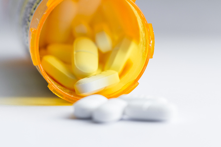 close up of a group of white tablets with an out of focus prescription bottle in the background Stock Photo - 90341063