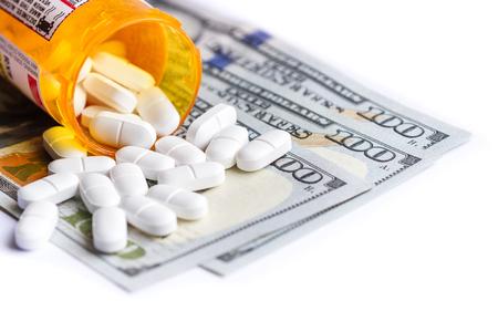 cerca de una botella de prescripción con mesas blancas cayendo en la parte superior de un grupo de cien billetes de un dólar
