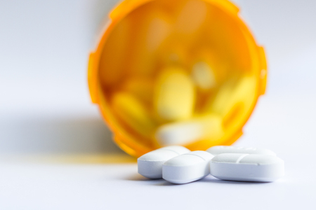 close-up van een groep van witte tabletten met een onscherp recept fles op de achtergrond