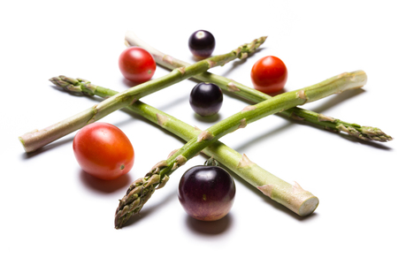 concept for healthy food games using asparagus and tomatoes to play tic tac toe
