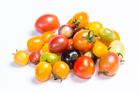 cluster of small cherry tomatoes in a variety of colors isolated on a white background Stock Photo