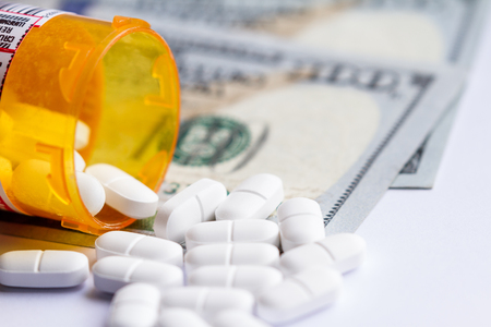 close up of a prescription bottle with white tables falling out on top of a group of hundred dollar bills