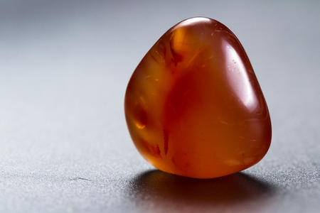 Close up of a polished piece of carnelian isolated on a black background Stock Photo