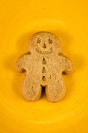 close up of a smiling ginger bread man cooks on a yellow plate Stock Photo