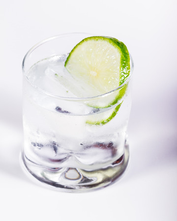 close up of a short tumbler glass with a clear liquid and a lime wheel as a garnish