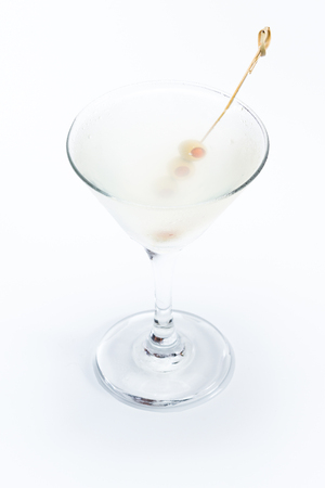 Freshly poured dirty vodka martini with green olives served on a chilled glass isolated on a white background
