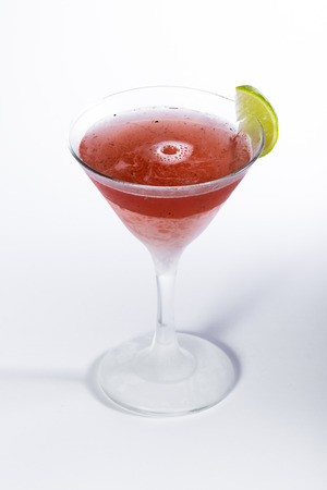 close up of a red cocktail served in a martini glass isolated on a white background