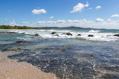 relaxing beach scene in Playa Grande Costa Rica with waves crashing into the rocks with crystal clear water Banco de Imagens