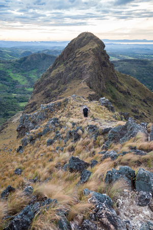 Hikers almost at the top of Cerro Pelado in Costa Rica, early morning shot with the rocky terrain and dried grass blowing in the wind. Stock Photo