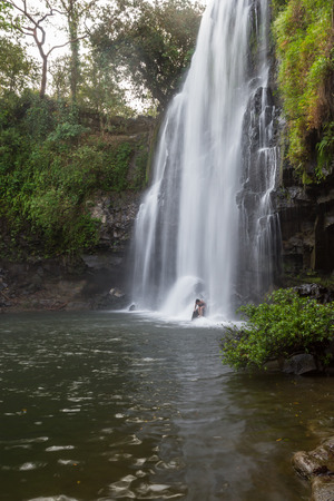 Llanos del Cortez waterfall in Costa Rica with a person standing at the base to show the size of the falls Фото со стока