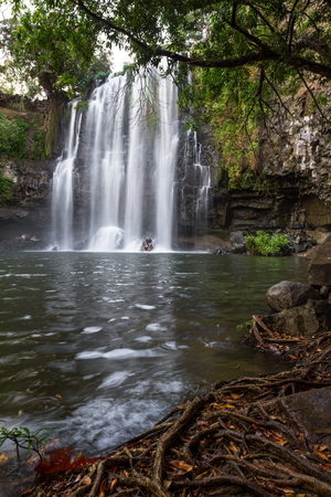 couple enjoying a dip in the warm water of this beautiful waterfall in Costa Rica, Llanos del Cortez Фото со стока