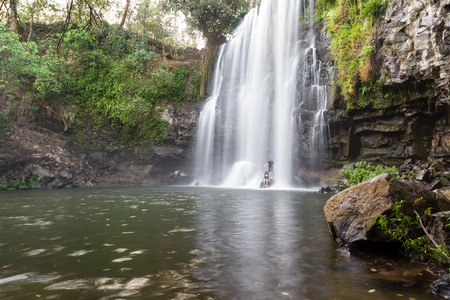 couple enjoying a dip in the warm water of this beautiful waterfall in Costa Rica, Llanos del Cortez Stock Photo