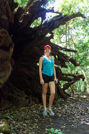 young woman standing next to a large fallen tree in the rainforest of Costa Rica