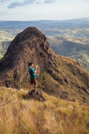 Man capturing the views of Guanacaste Costa Rica from the top of this local treasure, Cerro Pelado at sunset Stock Photo