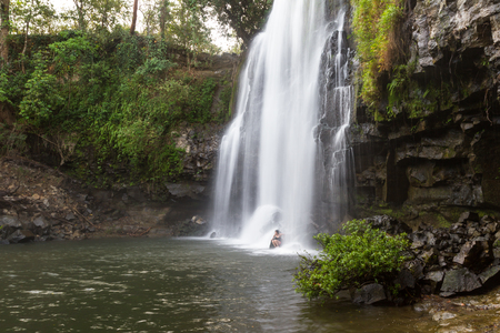 Llanos del Cortez waterfall in Costa Rica with a person standing at the base to show the size of the falls Stock Photo