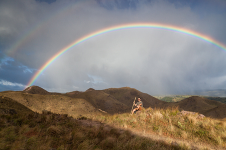 hiker taking time to pose and enjoy the view of a beautiful vivid rainbow on top of the mountains in Canas, Guanacaste Costa Rica Banco de Imagens
