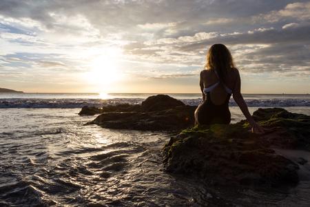 attractive woman sitting on the rocks enjoying a beautiful sunset in Playa Flamingo, Costa Rica