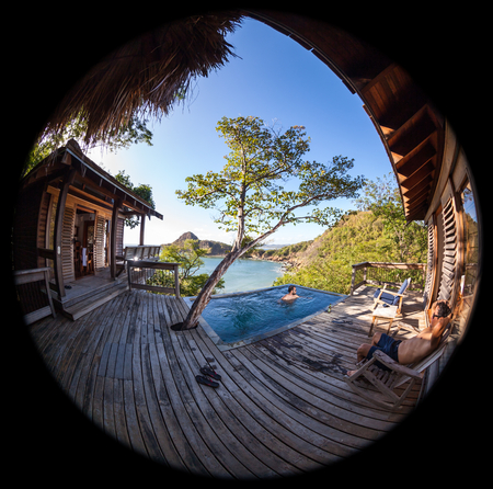 two men relaxing in a peaceful pool overlooking the pacific ocean in Nicaragua shot with a fisheye lens creating a circl=ular effect Stock Photo