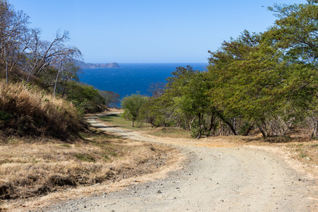 beautiful blue waters of the pacific ocean in Costa Rica with an unpaved road that leads down to the beach