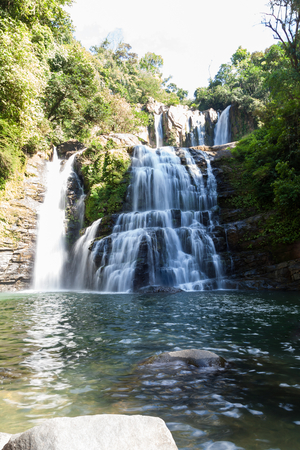 Nauyaca waterfalls with a deep swimming hole and large rocks in the south pacific of Costa Rica, a popular hiking destination.