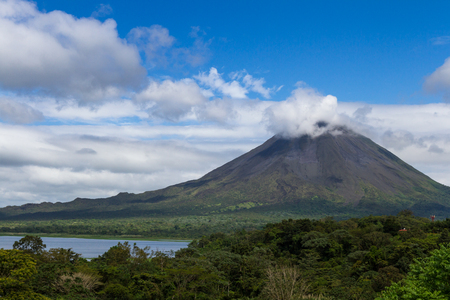beautiful view of the Arenal Volcano from an elevated view point showing a green tropical rainforest at the base