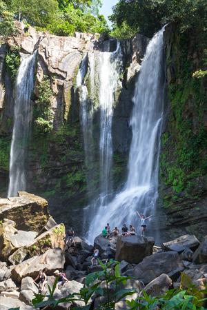 Nauyaca, Costa Rica - January 28: People sitting on the large boulders at the base of the falls. January 28 2018, Nauyaca, Costa Rica