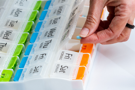 details of a hand carefully organizing prescriptions pills for a weekly dose Stockfoto