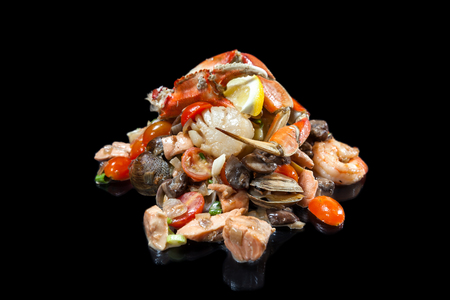 sautéed mixed seafood piled high o a mound isolated on a black background