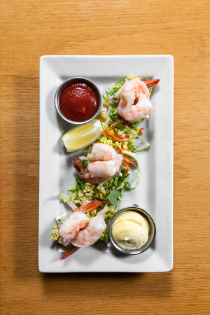 serving of a prawn or shrimp cocktail appetizer on a bed of greens and tartar and cocktail sauce for dipping