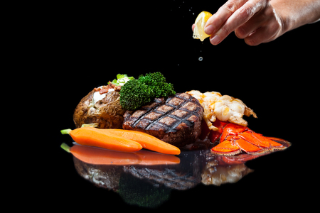 grilled lobster and filet mignon served with a loaded baked potato and vegetables isolated on a black background 免版税图像