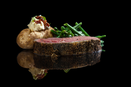 Rare prime rib served with a loaded backed potato and green beans on a black background Stock Photo