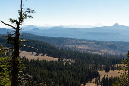 view from Crater Lake national park at a section of forest that burned last year and smoke in the mountains from a recent wildfire near California Stock Photo